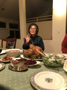 Janet's mom, an Asian woman wearing glasses, smiles and waves from behind a picture-perfect Thanksgiving turkey.