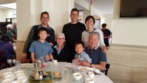 Lindsay's family - gathered last year. Lindsay is in the back to the right of two men, in the foreground are two children and two elders. Everyone is smiling.
