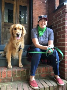 Erika, wearing a green bandana, sits on a brick stoop with a Golden Retriever who has a green leash on. They're both smiling at the camera.