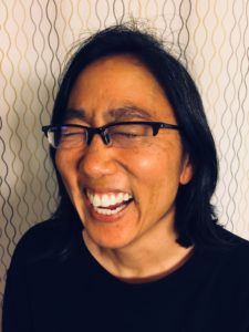 Stacy, a brown woman in glasses, is laughing and smiling really big.