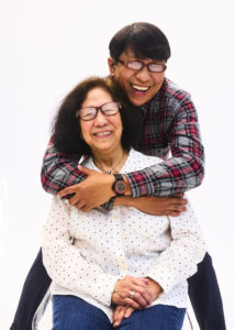 Allen Galeon, a Filipino care worker and family caregiver, is leaning over and hugging his mother, Pura Sherri Bloom, a former home care worker, who is seated in front of him. Allen is wearing a red and grey plaid shirt, glasses, and black pants, and Pura is wearing a white polka dot shirt and jeans.