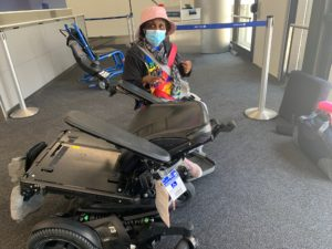 Engracia, in the background, seated in a temporary wheelchair, faces the camera and is wearing a pink hat and mask. In front of her is her broken power wheelchair, with the backrest completely bent back.