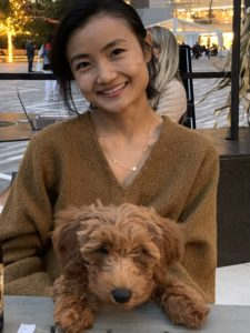 Yeen, wearing a brown sweater and smiling, is seated and holding Milo, a brown fluffy dog.